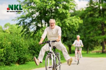 aktives Alter, Menschen und Lifestyle-Konzept - glückliches Seniorenpaar, das Fahrräder im Sommerpark reitet. Rentenlotterie Gewinn.