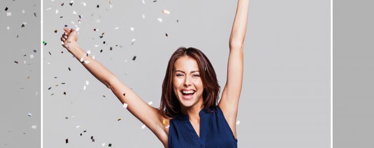 Frau freut sich über Lotto-Gewinn und wirft vor Konfetti die Arme in die Luft.