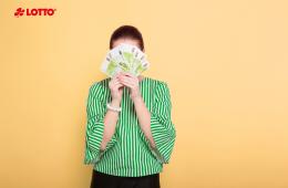 Geschäftsfrau mit Haarbun. Anonyme Frau versteckt sich hinter 100 Euro scheinen. Sie hat den Lotto-Jackpot gewonnen.