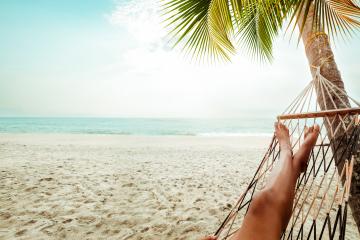 Freizeit im Sommer - Schöne gebräunte Damenbeine. Entspannen Sie sich an einem tropischen Sandstrand auf der Hängematte bei einer Palme. Vintage-Farbstile. Freizeit im Sommer - Schöne Tannenbeine von sexy Frauen. Entspannen Sie sich an einem tropischen Sandstrand auf der Hängematte. Vintage-Farbstile