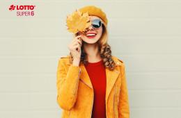 SUPER 6: Lotterie.de-Kundin gewinnt 100.000 €. Lachende Frau in gelber Kleidung und mit Sonnenbrille hält ein Blatt über ihr Gesicht. Links oben sind in der Ecke das Lotto- und Super 6 Logo zu sehen. SUPER 6: Lotterie.de-Kundin gewinnt 100.000 €