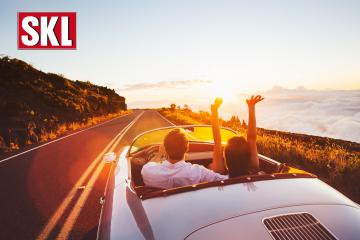 Lotterie-Gewinne im September 2020. Paar sitzt in einem silbernen Cabrio und fährt auf einer weiten Straße dem Sonnenuntergang entgegen.