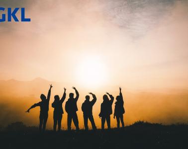 Gruppe von Menschen steht bei sonnenuntergang auf dem Berg. Sie freuen sich über den Gewinn beim Mililonenspiel. Oben Links sieht man das blaue Logo der GKL.